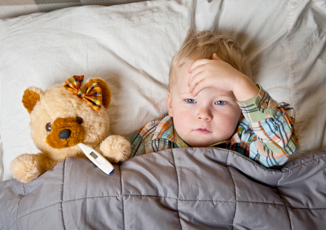 Child laying next to a teddy bear with a thermometer in bed