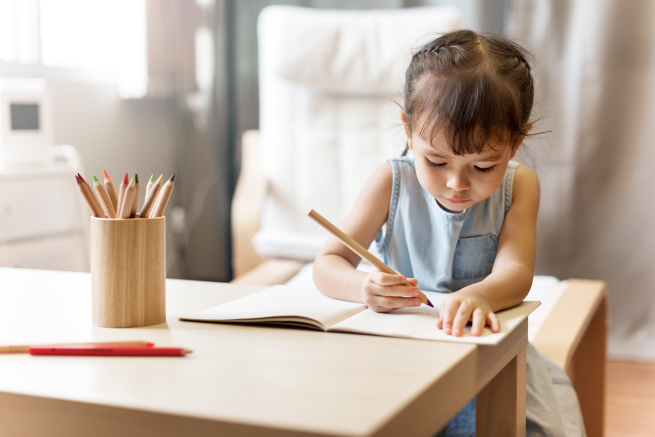 Child sitting at a table drawing